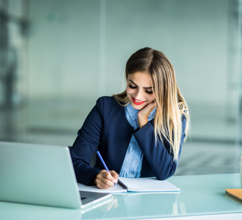 Young woman working with laptop and taking notes on a desktop at Office